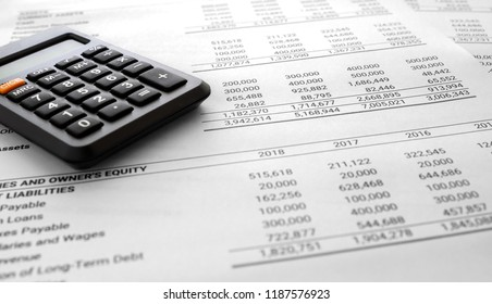 Financial statement / Balance sheet summary report and calculator, pen, laptop pc on auditor's desk. Accounting and accounts concept. document is mock-up.