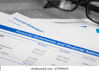 Financial statement letter on brown envelope and eyeglass, business concept; document is mock-up