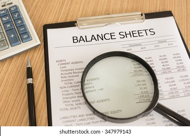 financial statement with magnifier, pen, summary report and calculator on auditor's desk.