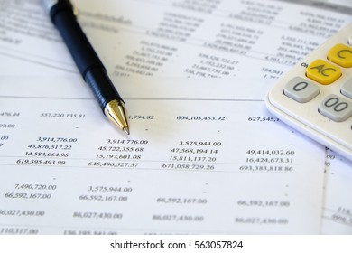 Financial statement reports with pen and calculator
