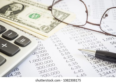 Financial statements, expend reports with modern pen, calculator, glasses and US money dollar. Concepts of accounting, audit , tax planning and marketing budget management.