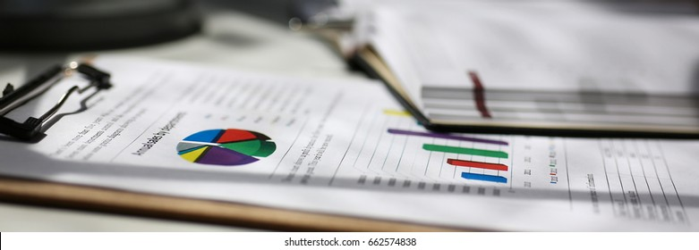 Financial statistics documents on clipboard pad at office table closeup. Internal Revenue Service inspector sum check, irs investigation, exchange market, earnings, savings, loan and credit concept