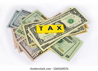 A financial still life with Dollar notes and the word 'tax' on a white background.