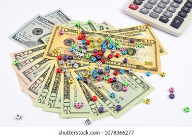 A financial still life with Dollars banknotes with smaill dice on top and a calculator. A metaphor on Financial risk.