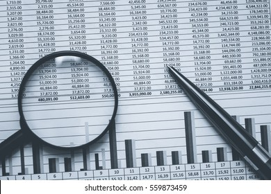 Financial stock banking accountant spreadsheet data in black and white. Conceptual monochrome photo with magnifying  glass and black metal pen.
