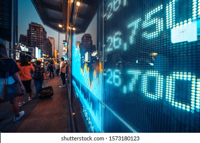 Financial stock exchange market display screen board on the street  with city scene reflect on glass