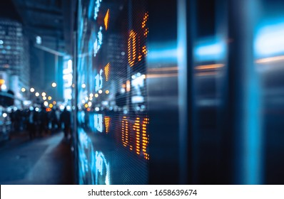 Financial stock exchange market display screen board on the street with and city light reflections, selective focus