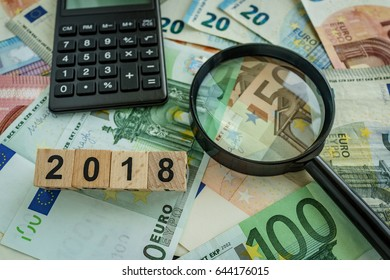 financial tax concept as magnifying glass on pile of euro banknotes, calculator and number 2018 on wooden block.