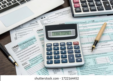 Financial time tax form with laptop and calculator. Office paperwork. Accounting