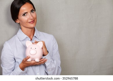 Financial woman holding pink piggy bank in button down shirt and looking at camera on grey texture background
