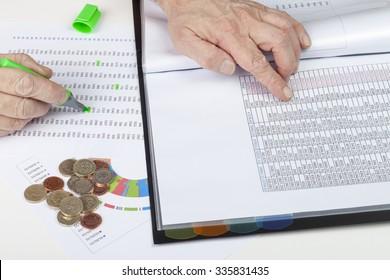 Financier at desk cross referencing some sales ledgers