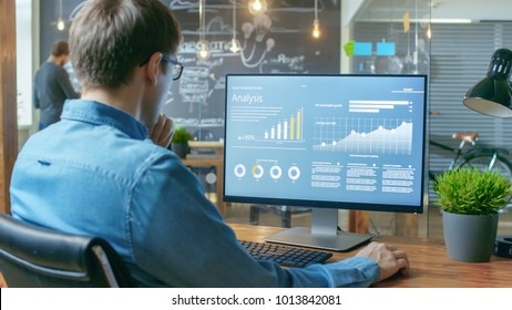 Financier Works on a Personal Computer Showing Statistics, Graphs and Charts. In the Background His Coworker and Creative Office.
