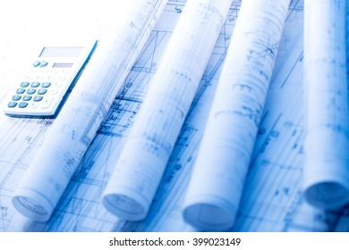 financing architectural project, blueprints rolls, calculator, pencil