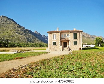 Finca rural vacation rental home with meadow in front surrounded by garden, road aside, blue cloudless sky