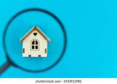 Find a home or a flat concept. Toy model house under magnifying glass. Rent apartments, Real Estate and buying a house idea. Blue background