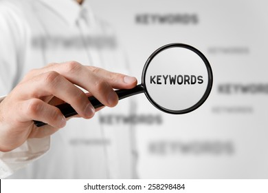 Find keywords concept. Marketing specialist looking for keywords (concept with magnifying glass).