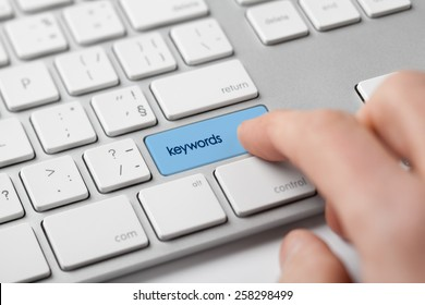 Find keywords concept. Marketing specialist looking for keywords (concept with keyboard).