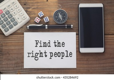 Find the right people written on paper,Wooden background desk with calculator,dice,compass,smart phone and pen.Top view conceptual.