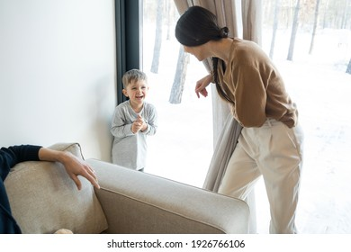 I find you. Happy active young brunette woman wearing casual outfit catching her son while playing at the peekaboo at the living room. Family activities concept