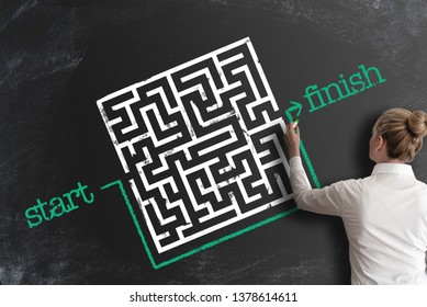 finding creative and smart solutions concept with woman bypassing labyrinth by drawing line around it as workaround on blackboard