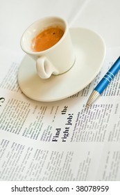 Finding a job with cup of coffee and newspaper