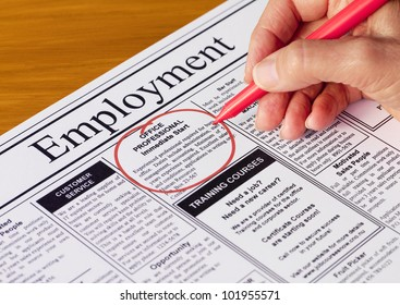 Finding a job in the employment section of the newspaper (newspaper created by photographer)