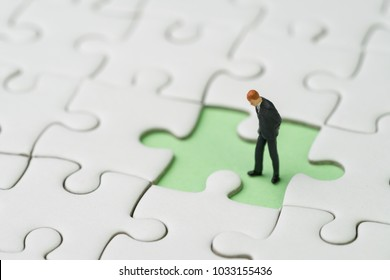 Finding the missing piece for business success concept, miniature people businessman standing and looking at the missing white jigsaw puzzle piece on pastel green background.
