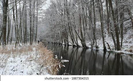 Finding solitude in the wilderness. Amazing forest and river landscape in winter. A silhouette of a fisherman in the distance. - Shutterstock ID 1887304315