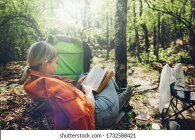 Trouver la solitude dans le concept de la nature sauvage. Une jeune femme se reposant en forêt, assise dans un fauteuil de camp et lisant un livre