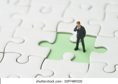 Finding solution for business problem to be success concept, miniature people businessman standing and thinking at the missing white jigsaw puzzle piece on pastel green background.