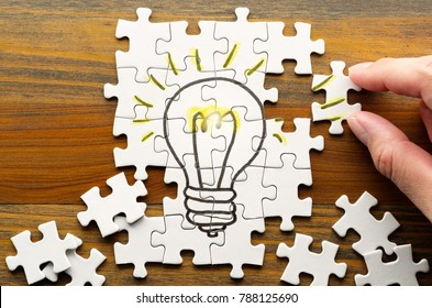 Finding solution. Solving puzzle on wooden desk. Idea creation. Light bulb drawn on puzzle.