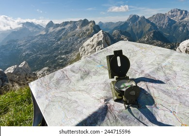 Finding your way with a compass and a map on the top of the mountain Rombon, Slovenia