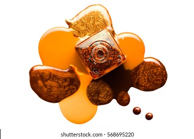 Fine art beauty concept of orange and brown metallic coppery nail varnish puddled artistically around an open bottle viewed from overhead isolated on white with copy space