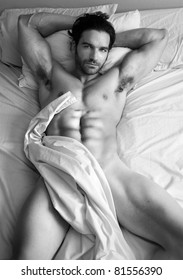 Fine art black and white body portrait of a nude male model in bed