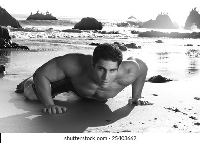 Fine art black and white photo of a young muscular man crawling on beach