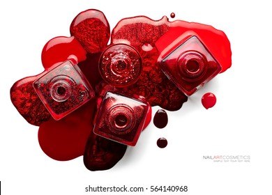Fine art cosmetics and beauty image. Nail art concept with a set of trendy red nail polish spilled around four opened bottles viewed top down, different shades and metallic lustre isolated on white
