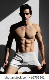 Fine art fashion portrait of a young muscular man in the shadows and light