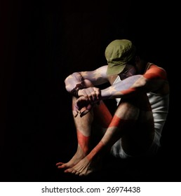 Fine art full body portrait of a soldier in American flag body paint and green army hat against black background