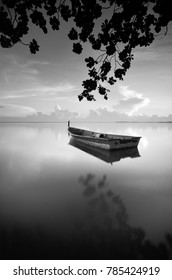Fine art image in black & white of traditional fishing boat with nature framing at Tumpat Kelantan, Malaysia. Soft Focus due to long exposure.