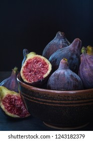 Fine art image of ripe purple figs in a rustic ceramic bowl with one fig sliced through to show the succulent flesh and pips