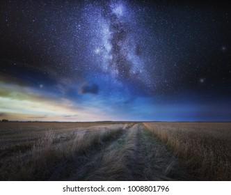 Fine art landscape with starry sky over stubble field. Beautiful dreamy landscape.