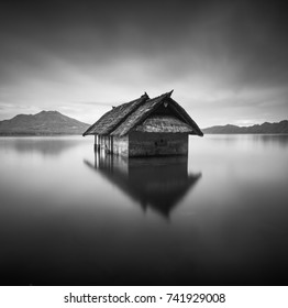 Fine art or minimalist of a floating house waiting to sink on lake in black and white. Located at Lake Batur, Kintamani Bali Indonesia. (blurry soft focus noise visible) Nature composition