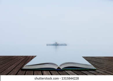 Fine art minimalist landscape image of derelict pier remains at sea during foggy morning giving appearance of ruins floating coming out of pages of open story book