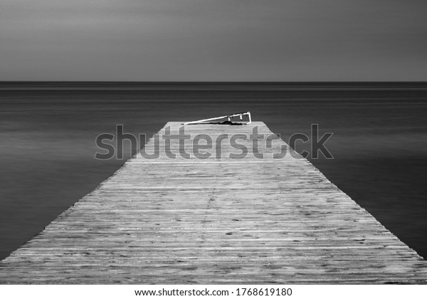 fine art photo of old wooden pier in smooth water with copy space