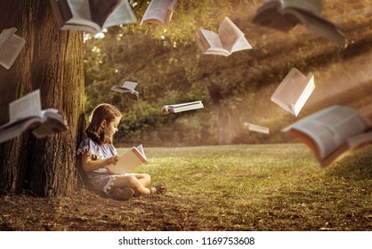 Fine art photo. Young girl reading a book in a park