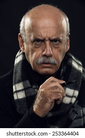 fine art portrait of an angry old man holding a pen in his hand.
