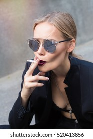 Fine art portrait of a beautiful lady with cigarette.Sexy woman in sunglasses and black jacket blowing smoke from a cigar. Swag style girl. Grey urban background, not isolated