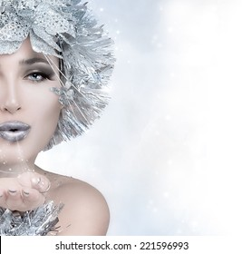 Fine art portrait of a gorgeous Christmas winter woman with cool grey makeup and a frost effect headdress blowing magic dust off her hand, close up partial face with copy space