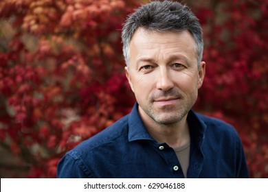 Fine art portrait of mid adult man looking at camera over nature background