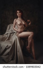 Fine art portrait of naked redhead woman sitting on an old armchair. Conceptual artistic photo of a sexy lady in a retro interior